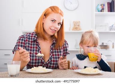 smiling mom eating porridge and feeding small girl indoors