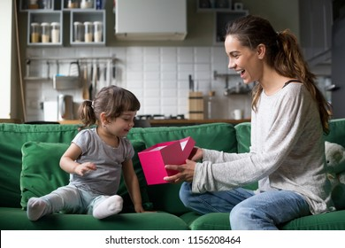 Smiling mom giving excited daughter present on her birthday, happy single mother and curious child girl opening pink gift box together, cute kid receiving holiday gift from mommy concept