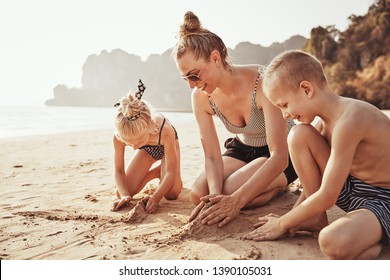 Smiling Mom and her two adorable children playing in the sand together during summer vacation at the beach