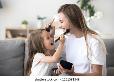 Smiling mom and kid preschool daughter doing makeup together, excited little girl holding make-up brush puts powder on mothers face, happy child applying blush having fun playing with mommy at home
