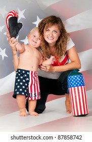 Smiling mom and son waving his hand on American flag background. Boy in boxer shorts with  boxing gloves and pear