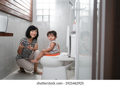 Smiling mother and baby look at the camera while watching videos on mobile phones with copyspace in the toilet