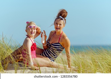 smiling mother and child in beachwear on the seashore applying suntan lotion. sunscreen SPF with broad range UV or bug repellent or insect bite remedy or hair protection leave-in SPF conditioner.
