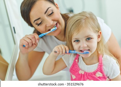 smiling mother and the child to brush their teeth in the bathroom