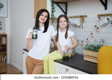 smiling mother with child daughter  drinks healthy green smoothie with straw in a jar mug in kitchen.