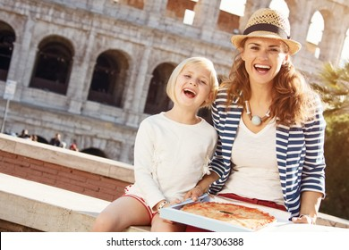smiling mother and child travellers in the front of Colosseum with pizza in the box