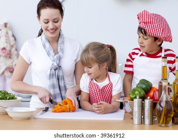 Smiling mother and children cutting vegetables in kitchen