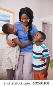 Smiling mother with children in living room at home