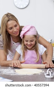 Smiling mother and daughter baking biscuits in the kitchen