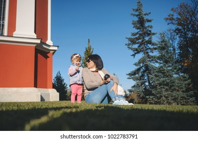 smiling mother and daughter having rest on green lawn