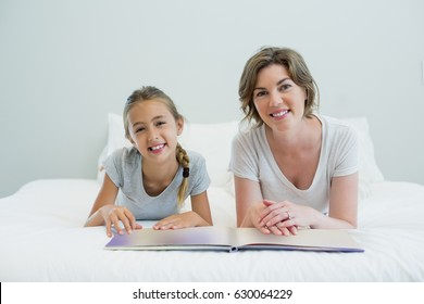 Smiling mother and daughter lying on bed and reading book in bedroom at home