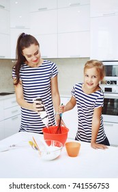 Smiling mother and daughter on a beautiful white kitchen dough blender knead