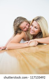 Smiling mother and daughter on the wooden floor