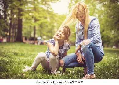 Smiling mother and daughter playing at park.