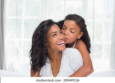 Smiling mother and daughter posing together on bed at home in bedroom