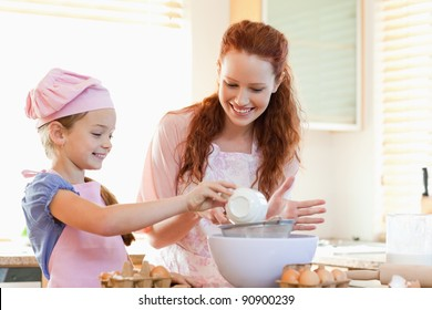 Smiling mother and daughter preparing dough together