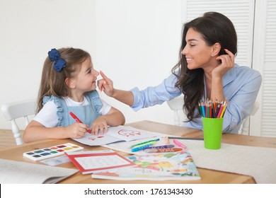 Smiling mother and daughter preparing for lessons and draws at the table with pencils and paints. Parent and pupil of preschool. First day of fall autumn. Girl from elementary class, back to school.