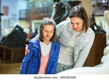 Smiling mother and daughter regarding ancient statues in museum