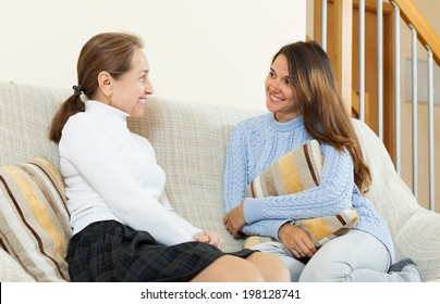 Smiling mother and daughter sitting on sofa at home and gossiping