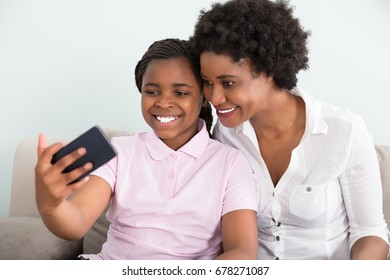 Smiling Mother And Daughter Taking Selfie On Smart Phone At Home