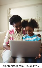 Smiling mother and daughter using laptop in living room at home