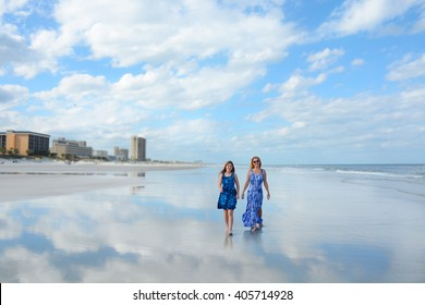Smiling mother and daughter walking on beautiful beach, hotels in the background, reflection of beautiful sky and clouds in the water on the beach, Jacksonville, Florida.