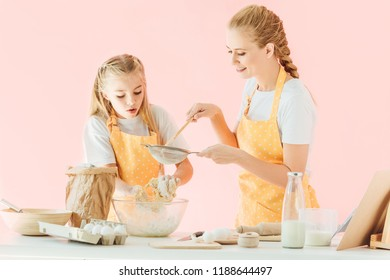 smiling mother and excited little daughter in yellow aprons preparing dough together isolated on pink