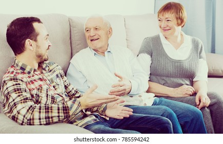Smiling mother and father and adult son spending quality time at home