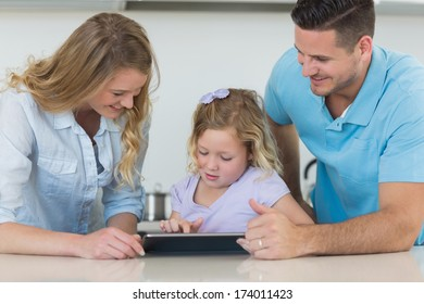 Smiling mother and father assisting daughter in using tablet PC at table