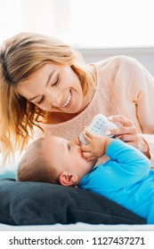 smiling mother feeding her little child with baby bottle on bed at home