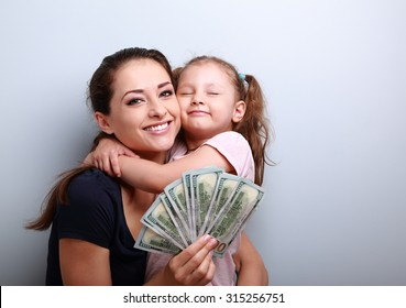 Smiling mother and happy cute daughter hugging and showing dollars. Happy winning family. Closeup portrait with empty copy space