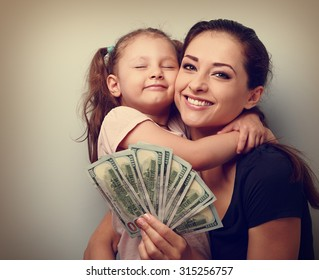 Smiling mother and happy cute daughter cuddling and showing dollars. Happy winning family. Vintage closeup portrait