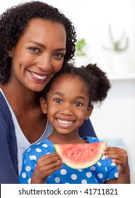 Smiling mother and her daughter eating fruit at home