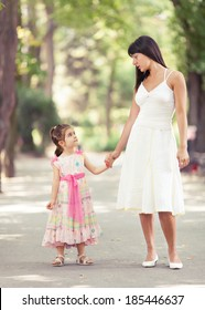 A smiling mother and her daughter are walking in the park and holding hands.