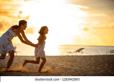 Smiling mother and her laughing young daughter playing on a tropical beach at sunset.