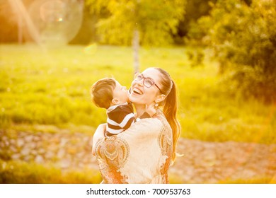 Smiling mother with her son in arms in the park. Family spending quality time together