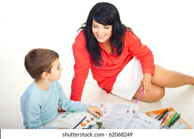Smiling mother and her son having conversation and sitting on floor with books and colorful pencils around them