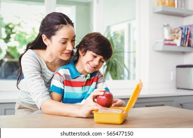 Smiling mother holding apple with son at table
