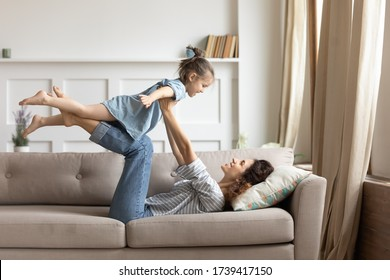 Smiling mother holding little daughter with hands outstretched pretending flying, lying on cozy couch in living room, family playing funny game, loving young mum carrying cute preschool girl