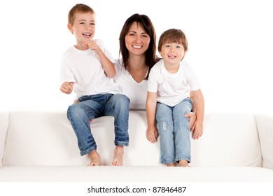 A smiling mother holds her happy pre-school children as they sit laughing on a white sofa.