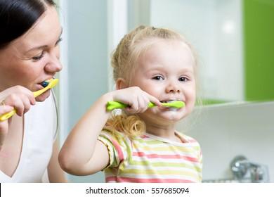 smiling mother and kid daughter brushing teeth in bathroom