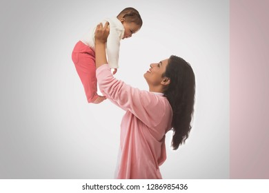 Smiling Mother lifting baby