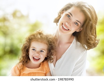 Smiling mother and little child on nature. Happy family outdoors