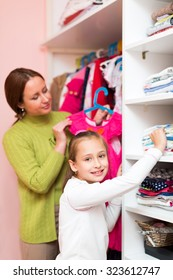 Smiling mother and little child staying near wardrobe with dresses on hangers.