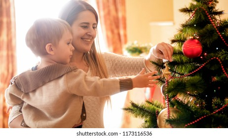 Smiling mother with little son decroating Christmas tree with baubles