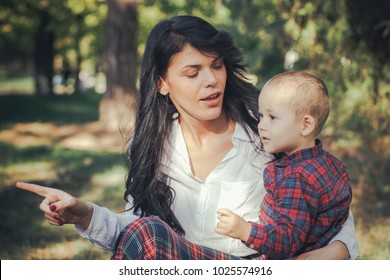 Smiling mother and little son playing together in a park. Mum hugging shy baby. Sunny  autumn day. Close up. Copy-space. Outdoor shot.Happy family