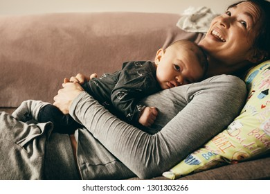 Smiling mother lying on couch with her baby sleeping on her chest. Happy mother relaxing at home with her child sleeping on her.