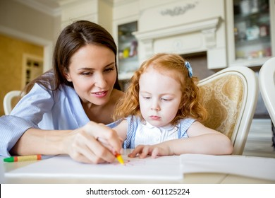 Smiling mother or nanny drawing with little girl