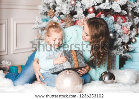 Smiling mother open Christmas presents with kid daughter over Christmas  tree in room. 532f403d2