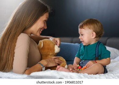 Smiling mother playing with her cute toddler son at home in the bed. Using plush bear and baby toys. Maternity concept. Playing with children.